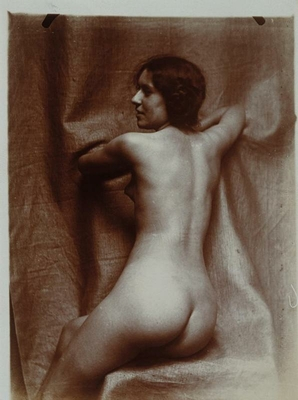Naked woman sitting three-quarters back, on a chair, face in profile left